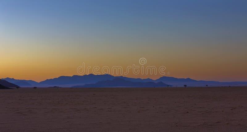 Blauwe bergen en gele hemel na zonsondergang in de woestijn stock afbeeldingen