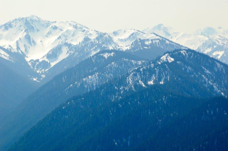 Blauwe bergen en sneeuw afgedekte pieken royalty-vrije stock afbeeldingen