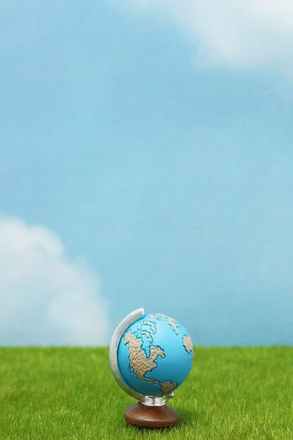 Blauwe bol op groen gras over blauwe hemelachtergrond stock fotografie