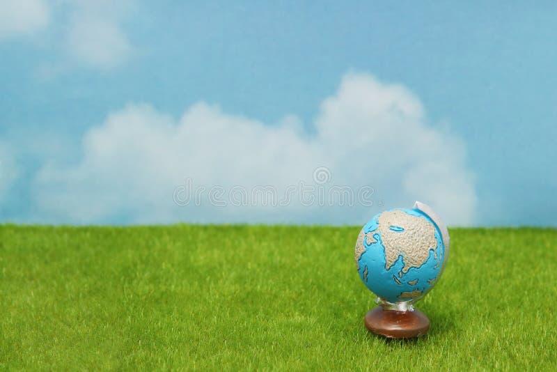 Blauwe bol op groen gras over blauwe hemelachtergrond stock afbeelding