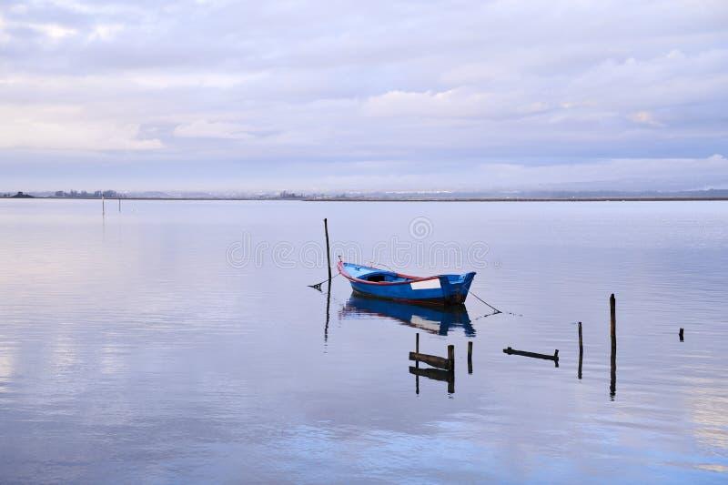 Blauwe boot in het midden van het meer stock afbeeldingen