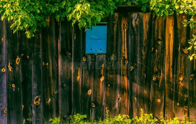 Blauwe brievenbus op een houten omheining royalty-vrije stock fotografie