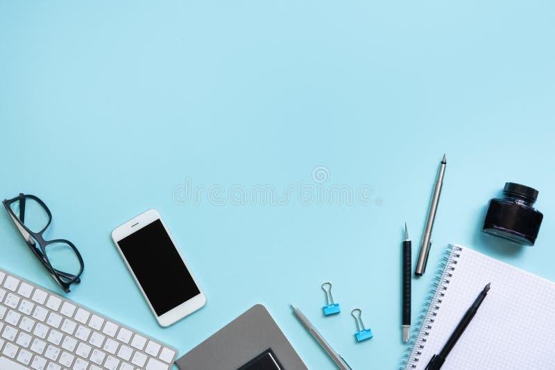 Blauwe bureaulijst met leeg notitieboekje, smartphone, computertoetsenbord en andere bureaulevering stock fotografie