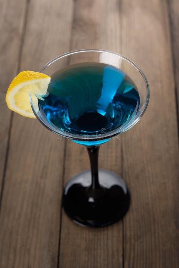 Blauwe cocktail in martini-glas met plak van citroen stock afbeeldingen