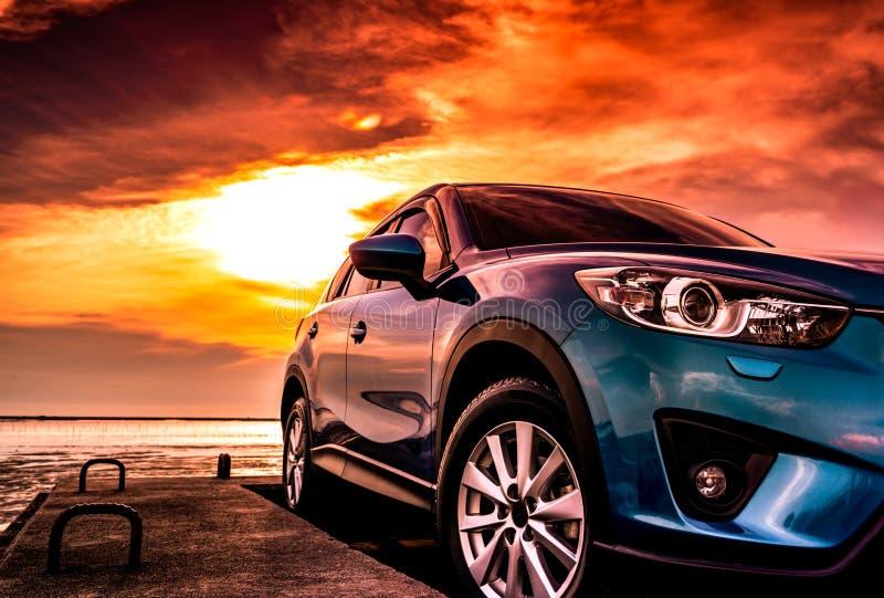 Blauwe compacte die SUV-auto met sport, moderne, en luxeontwerp op betonweg door het overzees bij zonsondergang wordt geparkeerd  royalty-vrije stock afbeeldingen