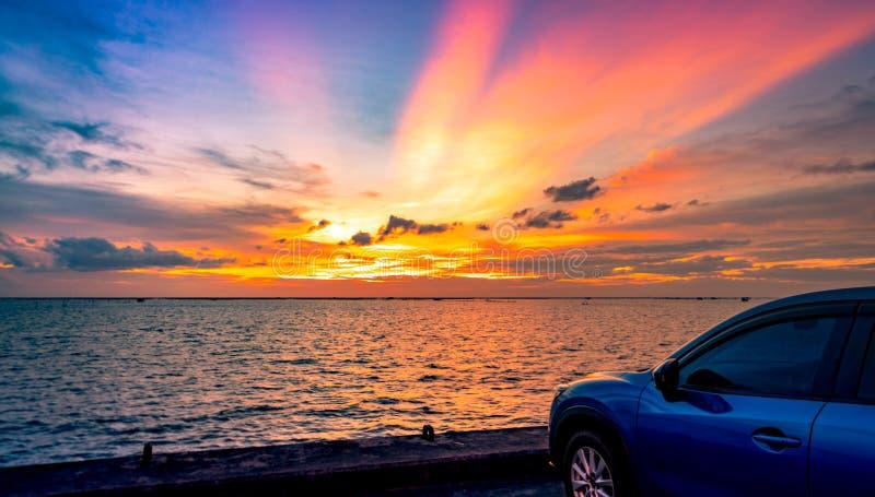 Blauwe compacte SUV-auto met sport en modern die ontwerp op betonweg door het overzees bij zonsondergang wordt geparkeerd De reis royalty-vrije stock foto