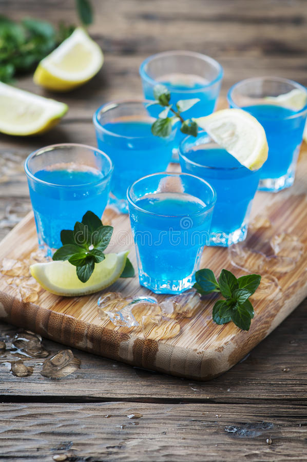 Blauwe curacao likeur met citroen op de houten lijst stock afbeelding