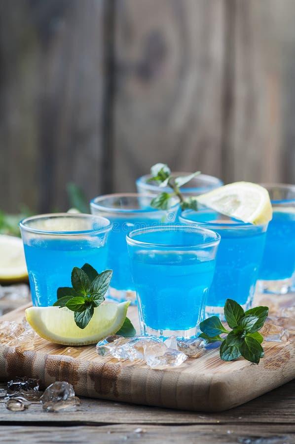 Blauwe curacao likeur met citroen op de houten lijst royalty-vrije stock afbeelding