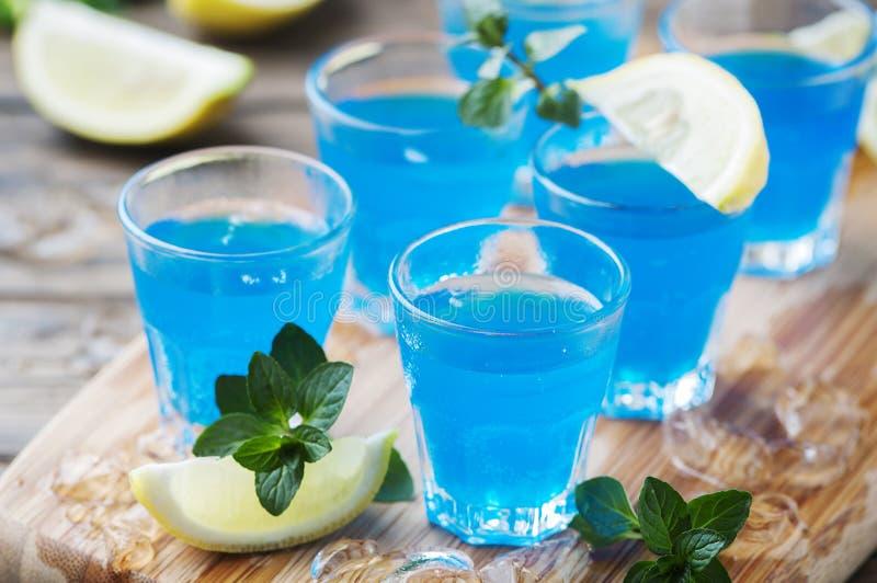 Blauwe curacao likeur met citroen op de houten lijst stock foto's