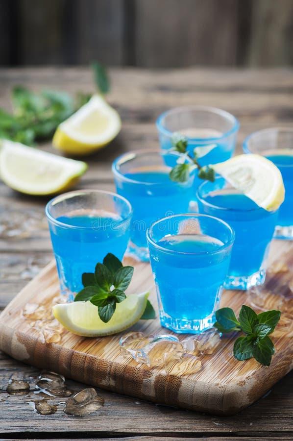 Blauwe curacao likeur met citroen op de houten lijst stock foto