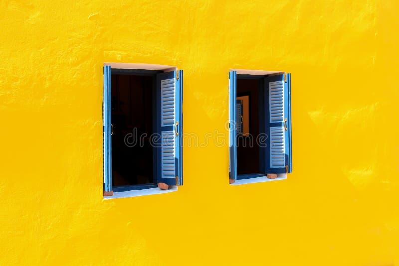 Blauwe de kleuren houten uitstekende stijl van het venstersblind die op de gele achtergrond van het muurcement voor decoratiearch royalty-vrije stock foto