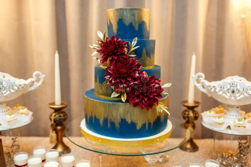 Blauwe die huwelijkscake door zich bloemen wordt verfraaid van feestelijke lijst met woestijnen te bevinden, aardbeitartlet en cu royalty-vrije stock foto