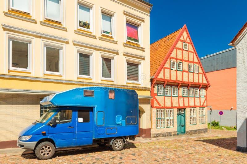 Blauwe die motorhome dichtbij een modern gebouw en een oud huis in de traditionele Duitse stijl wordt geparkeerd royalty-vrije stock afbeeldingen