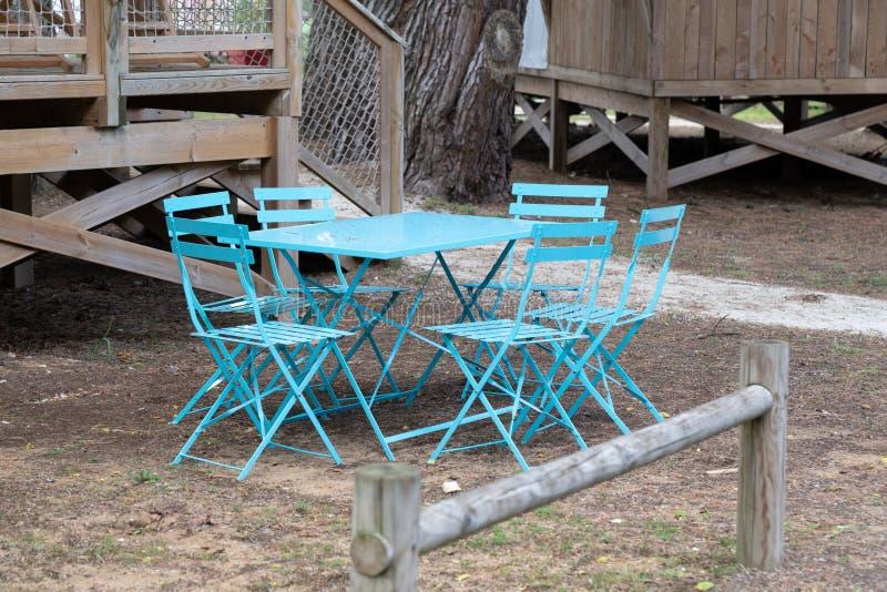 Blauwe die stoelen en lijst in metaalbuitenkant in de tuin van houten huthuis wordt gevestigd stock afbeelding