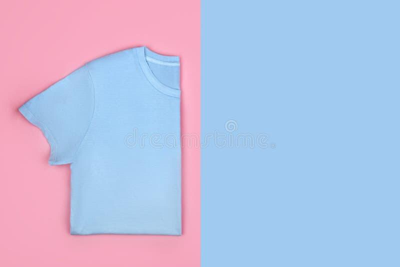 Blauwe die t-shirt op kleurrijke achtergrond wordt geïsoleerd stock afbeeldingen