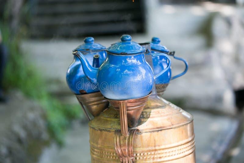 Blauwe die theepotten boven kopersamovar worden geplaatst stock afbeelding