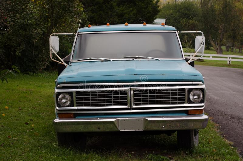 Blauwe die vrachtwagen aan wegkant wordt geparkeerd op het gras stock fotografie