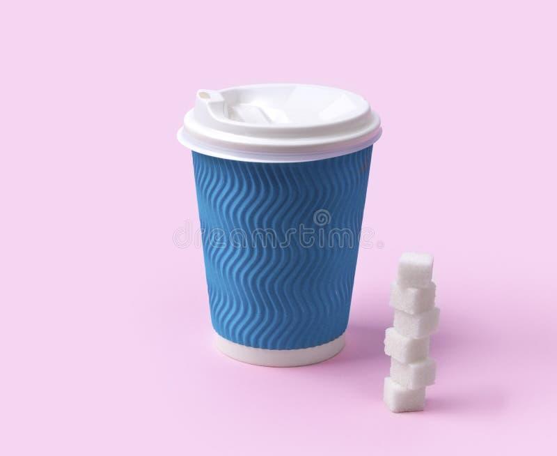 Blauwe document kop van koffie of thee met suikerkubussen bij roze achtergrond royalty-vrije stock foto's