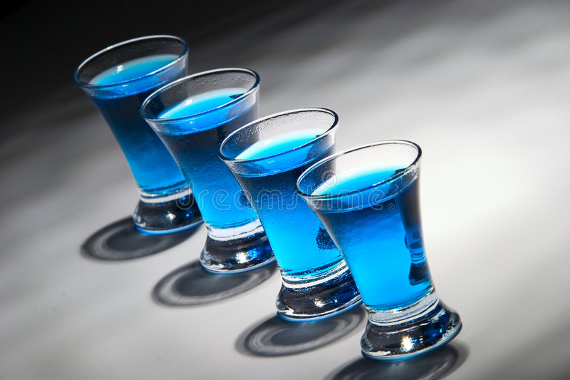 Blauwe drank vier in 4 glazen stock foto's