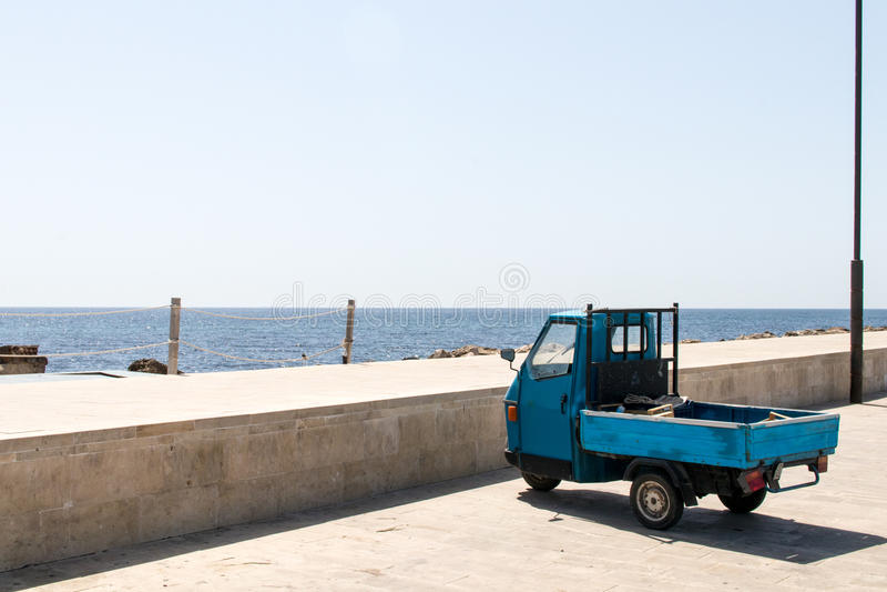Blauwe driewieler bij de haven dichtbij het overzees stock afbeelding