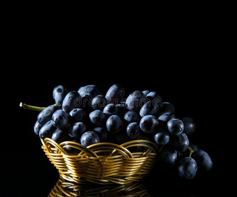 Blauwe druiven in een mand stock fotografie