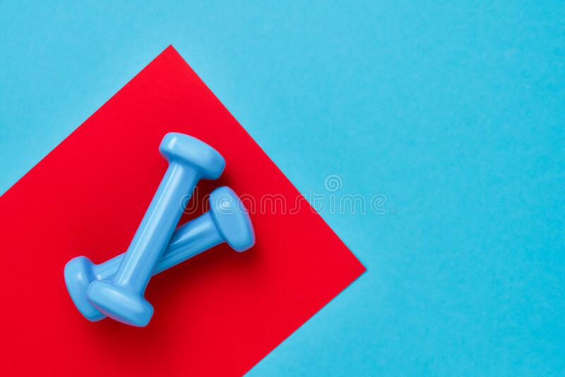 Blauwe dumbbels liggen op de rode blauwe achtergrond Het begrip gezonde levensstijl Kopieerruimte, bovenaanzicht stock afbeeldingen
