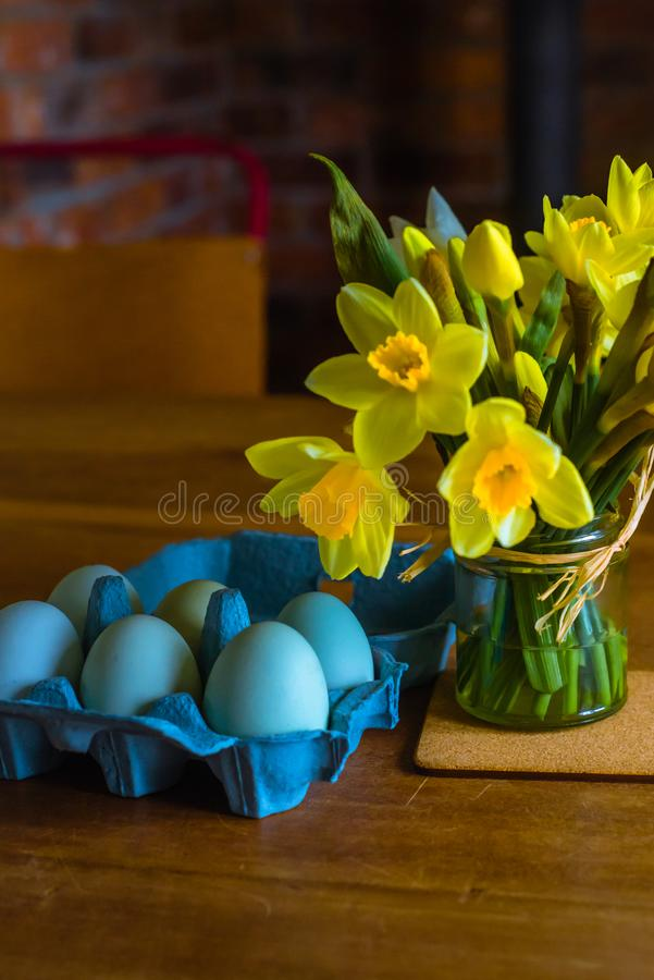 Blauwe Eieren en Gele Gele narcissen op een Keukenlijst stock foto