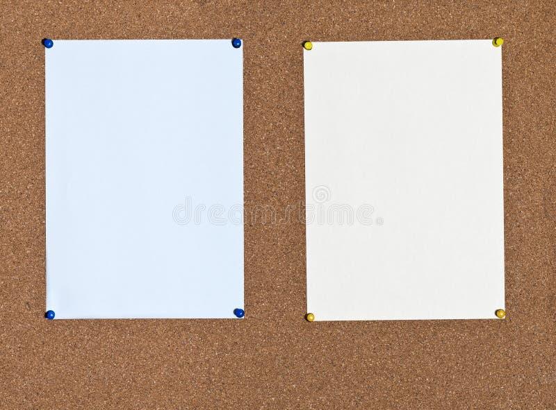 Blauwe en gele bladen van document op cork royalty-vrije stock afbeelding