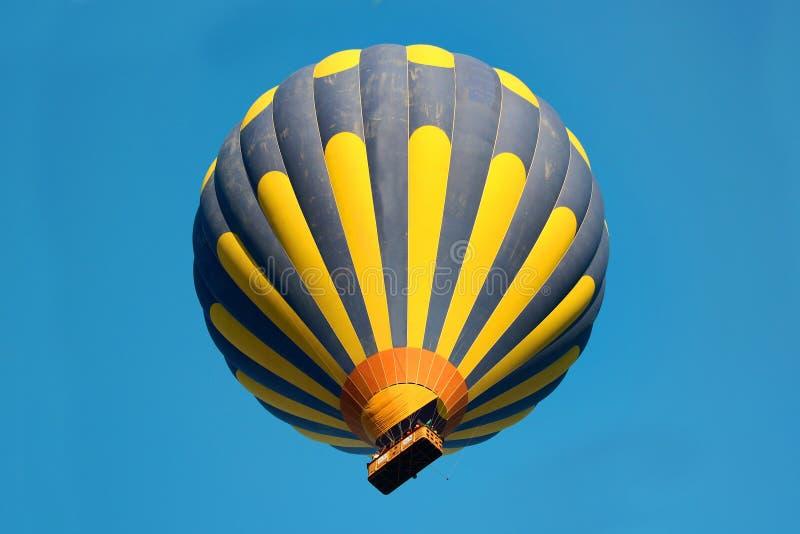 Blauwe en gele gestreepte ballon in de hemel stock foto