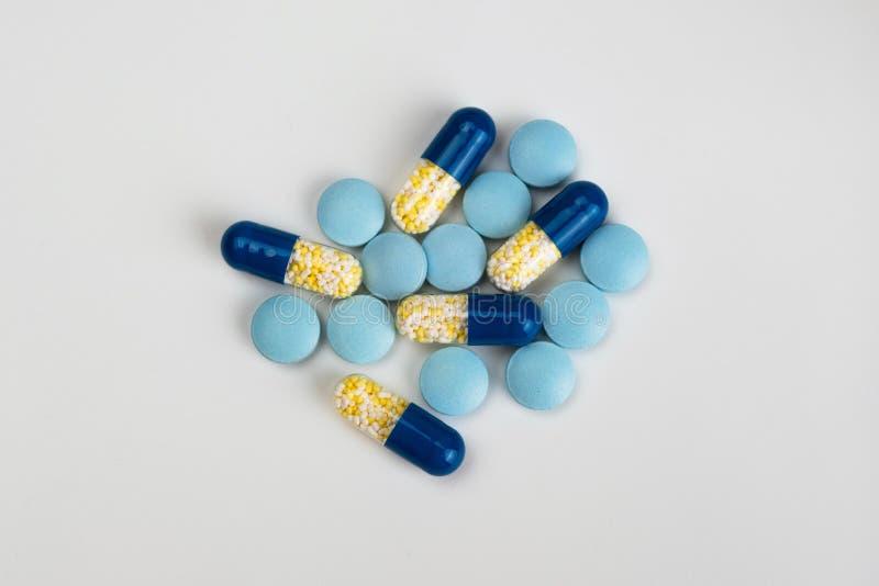 Blauwe en gele pillen en capsules op lichtgrijze achtergrond stock fotografie