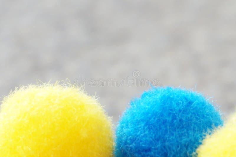 Blauwe en gele pom poms dichte omhooggaande mening over een grijze achtergrond met vrije ruimte voor tekst stock foto