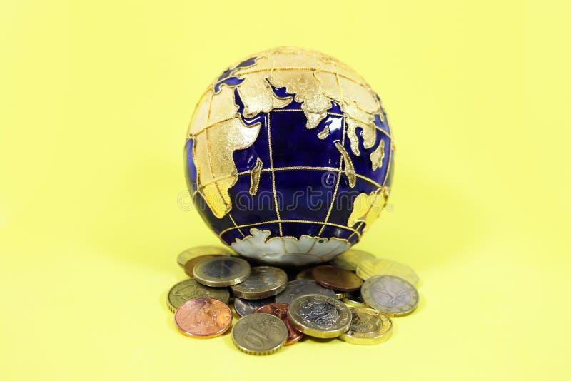 Blauwe en gouden bolzitting bovenop een stapel van een mengsel van muntstukken van de V.S. Europa en Groot-Brittannië stock foto's