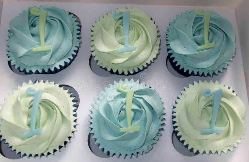 Blauwe en groene cupcakes met nummer 1 decoratie stock afbeeldingen