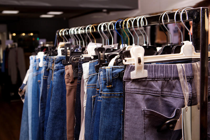 Blauwe en purpere jeans in een winkel stock foto
