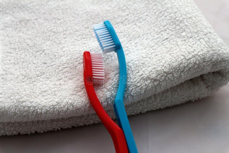 Blauwe en rode tandenborstels in omhelzing die op witte handdoek, het romantische concept van de valentijnskaartendag of paar in  stock foto