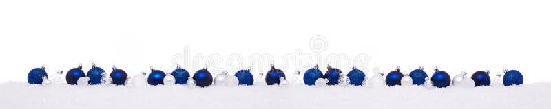 Blauwe en witte die Kerstmisballen op een rij op sneeuw worden geïsoleerd stock foto's