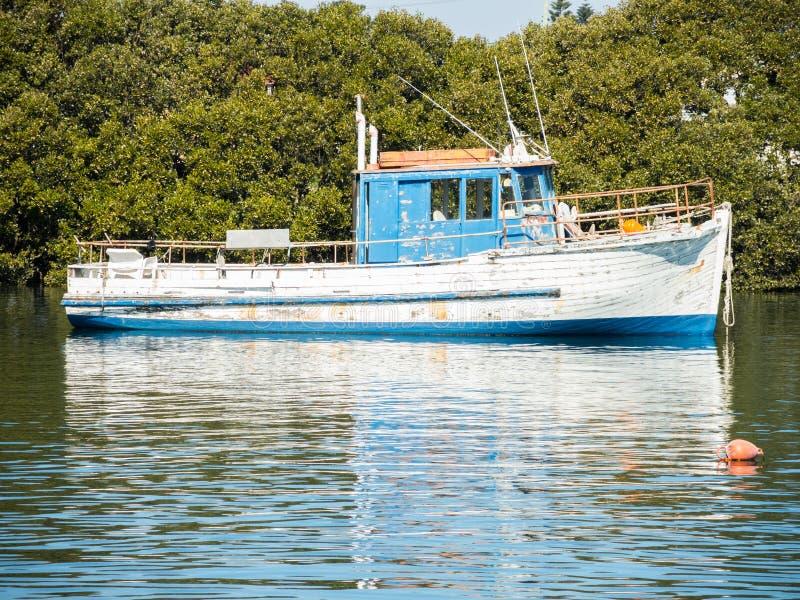 Blauwe en witte houten vissersboot in de haven alleen in Cook River, Sydney, Australië royalty-vrije stock fotografie