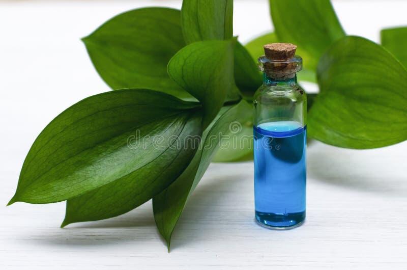 Blauwe essentie helende tint op witte houten lijstachtergrond Essentiële olie stock afbeelding
