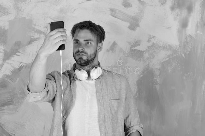 Blauwe eyed modieuze hipster met smartphone Amerikaanse knappe gebaarde kerel met hoofdtelefoons Muzikale levensstijl vrolijk royalty-vrije stock foto