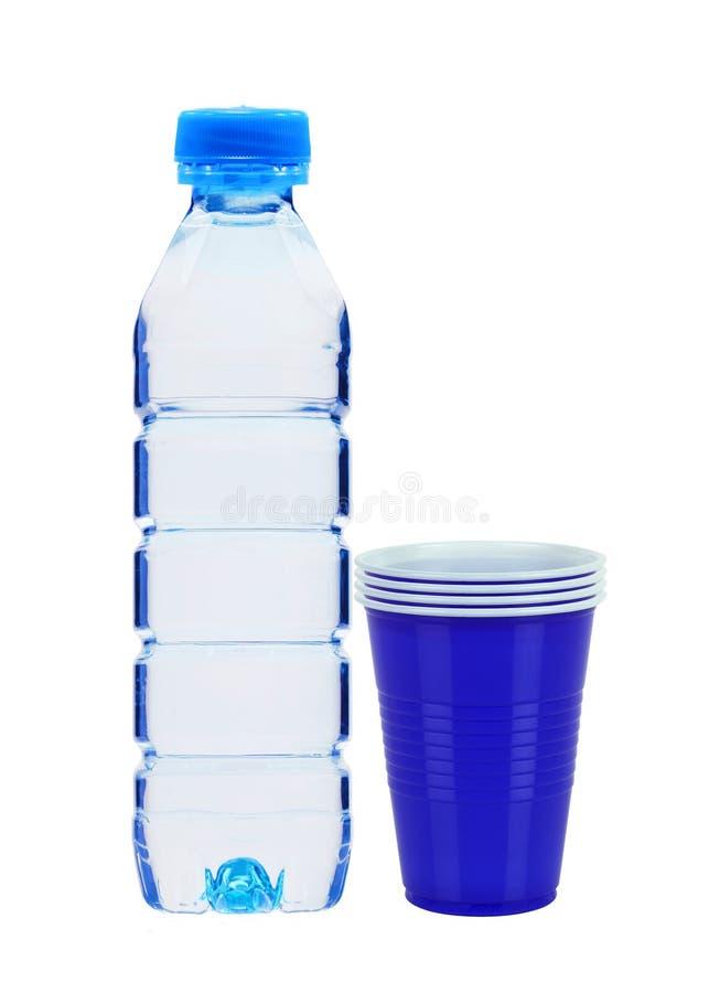 Blauwe fles met geïsoleerd water en plastic koppen stock foto's