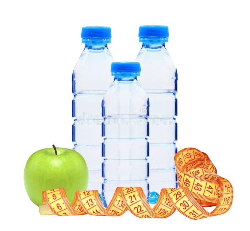 Blauwe flessen met water, maatregelenband en groene appel stock fotografie