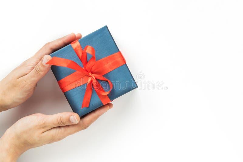 Blauwe Giftdoos met rood lint in de handen van de vrouw op witte achtergrond Hoogste mening Copyspace royalty-vrije stock foto