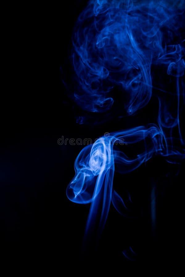 Blauwe giftige dampen op een zwarte achtergrond stock foto's