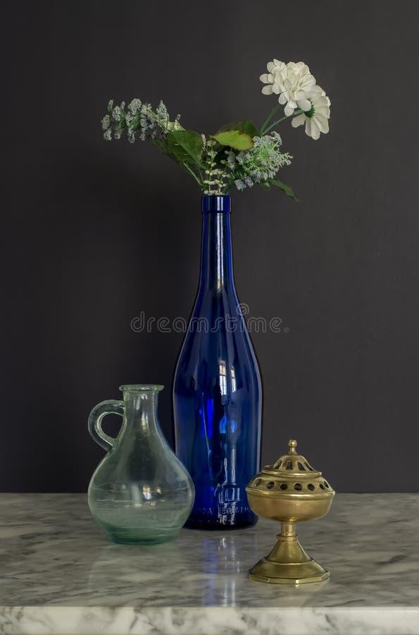 Blauwe glazen flacon met Flowers Brass Censer en Glass Jug Still Life royalty-vrije stock foto