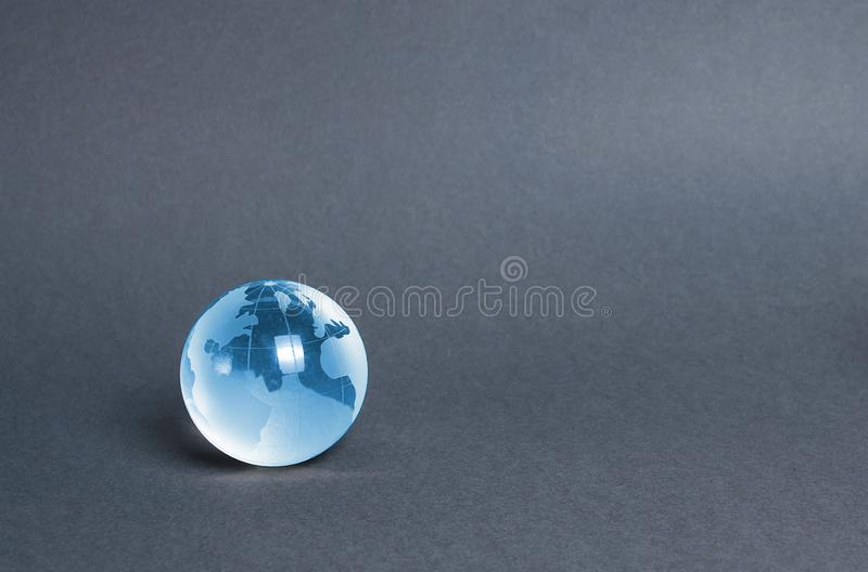 Blauwe glazen planeet gloed op een grijze achtergrond. Globalisering en markten. Bescherming van het milieu en vermindering van sc stock afbeeldingen
