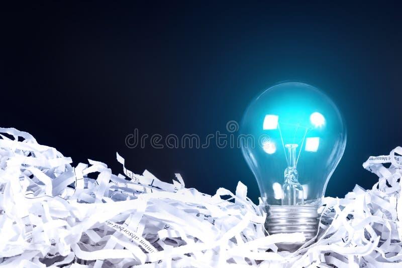Blauwe gloeilampen gloeiende plaats op verscheurd gerecycleerd document op bla royalty-vrije stock foto's