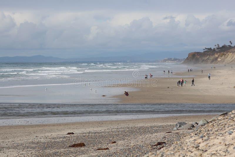 Blauwe grijze hemel langs het strand en de klippen stock afbeelding
