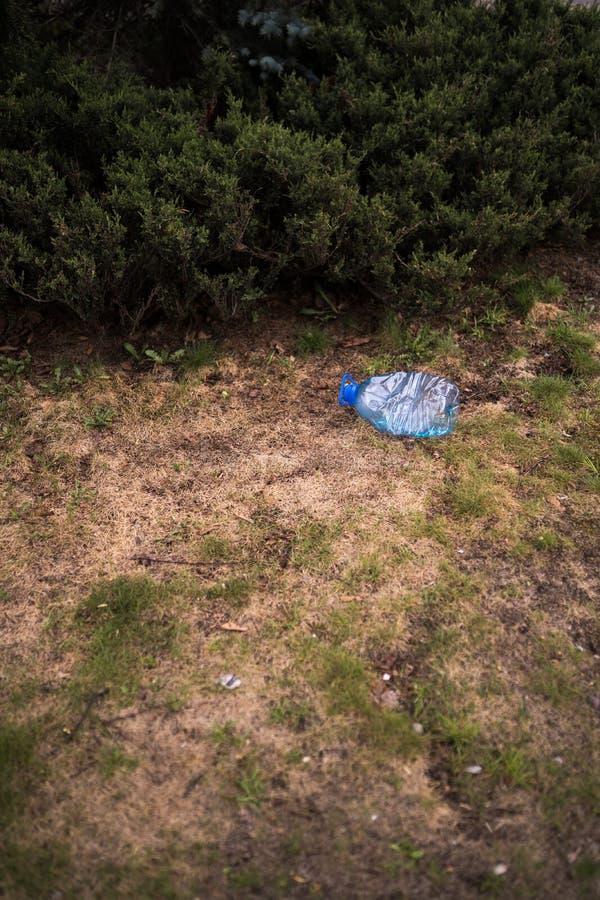 Blauwe grote plastic fles die op de grond in boom in een Weggegooid parkbos liggen - gerecycleerd niet - Afval en verontreiniging stock afbeelding