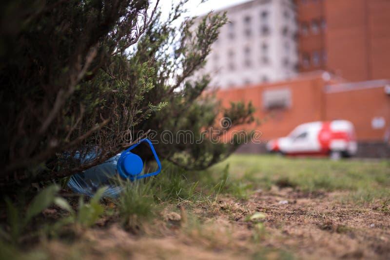 Blauwe grote plastic fles die op de grond in boom in een Weggegooid parkbos liggen - gerecycleerd niet - Afval en verontreiniging royalty-vrije stock afbeeldingen