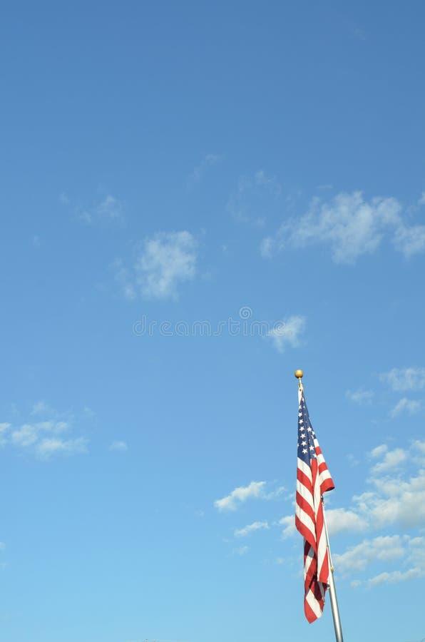 Blauwe hemel Amerikaanse vlag op poolverticaal stock fotografie